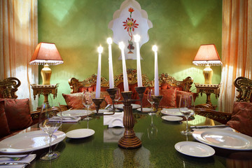 candlestick with five candles at glass table with serving, lamps