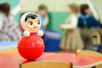 Bright red roly-poly toy stand at table in kindergarten