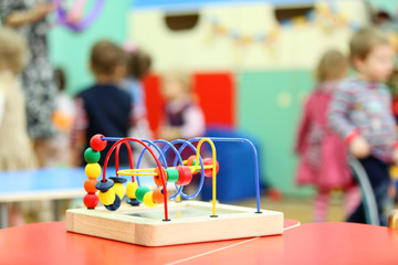 Colorful wooden toy stand at table in kindergarten;