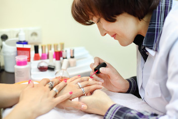 manicurist makes manicure for woman by pink nail polish in salon