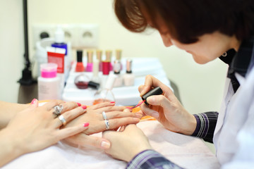manicurist manicures woman by pink nail polish in beauty salon