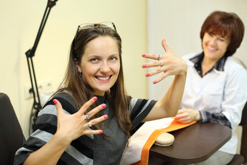 manicurist made manicure for woman in beauty salon;