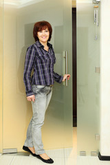 Happy woman dressed in shirt and jeans stands near door