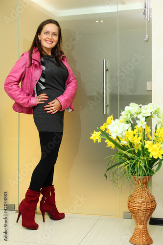 Happy woman dressed in pink jacket stands near transparent door;