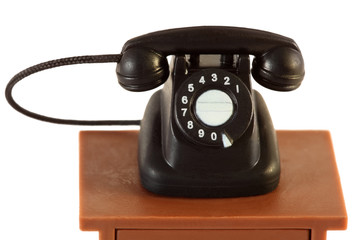 little retro black telephone on brown table isolated