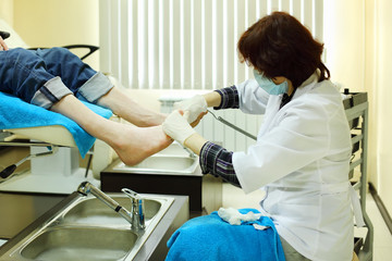Woman wearing white coat practices chiropody taking care of male