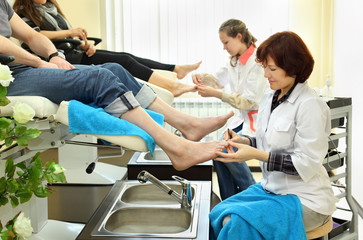 Two women wearing coats practices chiropody taking care of feet