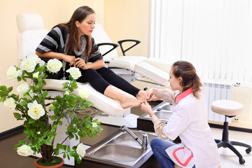 Woman wearing white coat practices chiropody taking care of feet