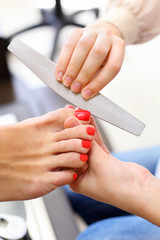 Female hands make pedicure by nail files for client in salon