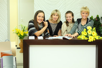 four smiling women sit in reception area with magazines