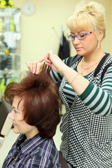 Hairdresser makes hair styling for woman by rake-comb in salon