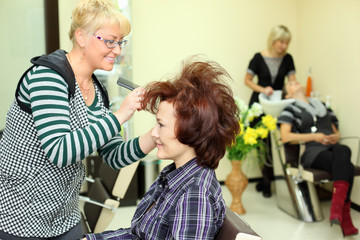 Smiling hairdresser makes hair styling for woman by rake-comb