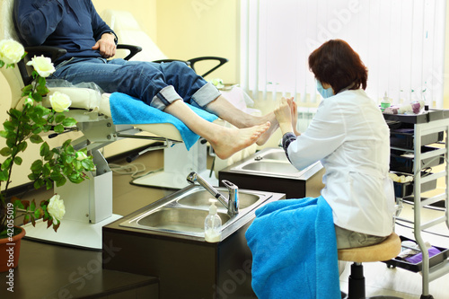 Woman wearing coat does foot massage for man in beauty salon