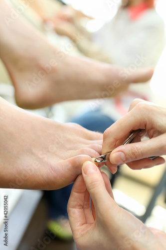 Female hands practicing chiropody taking care of male feet