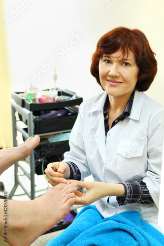 Woman wearing coat practices chiropody taking care of male feet