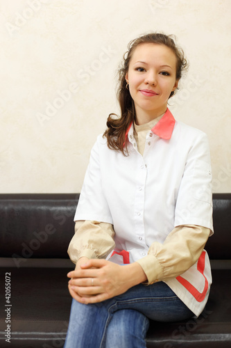 smiling girl dressed in white coat sits on black leather couch
