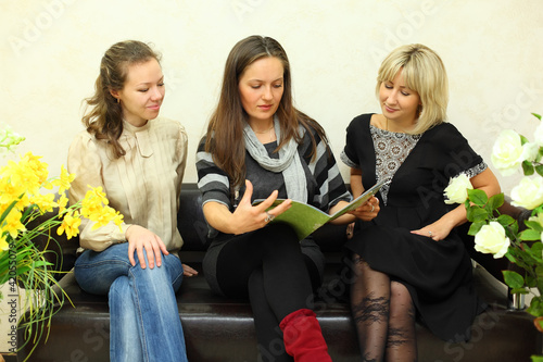 three young women sit on black leather couch