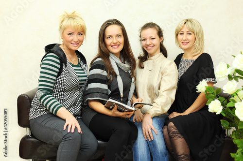 four smiling women sit on black leather couch and look at camera