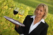 Waitress with red and white wine in a vineyard