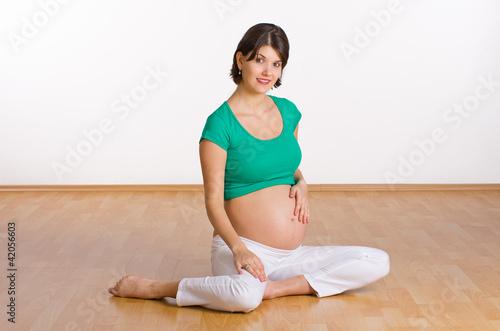 Schwangere sitzt auf dem Boden