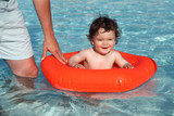 Baby in swimming pool with father