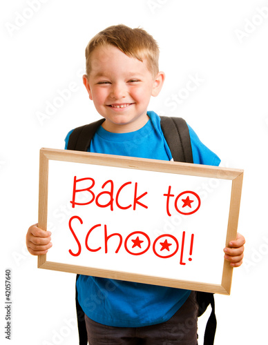 "Child holding sign that reads ""back to school"""