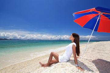 砂浜に座り寛ぐ女性