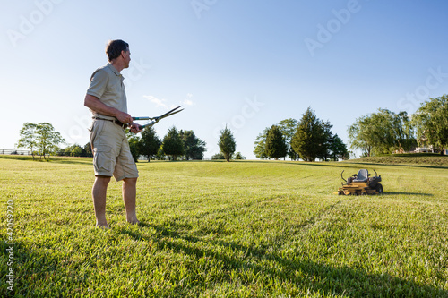 Senior man cutting grass with shears