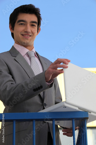 Businessman using his laptop on a balcony