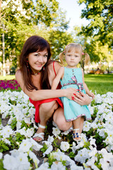young mother daughter relaxing sitting grass background