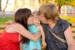 Beautiful happy family enjoying in the park, kissing baby