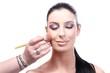 Makeup artist preparing beautiful woman's face