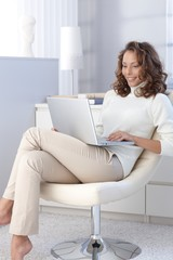 Attractive female with laptop at home