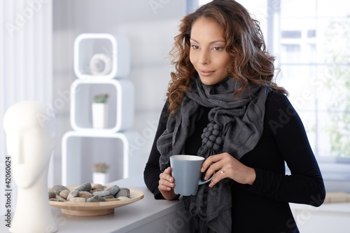 Pretty woman drinking coffee at home