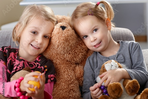 Little girls huddling up against teddy bear