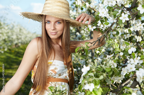 beautiful young woman standing near the apple tree on a warm sum