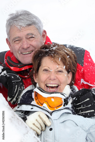 senior couple having fun under snow