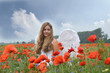 Happy Christmas: Angel on vacation in a field with red poppies