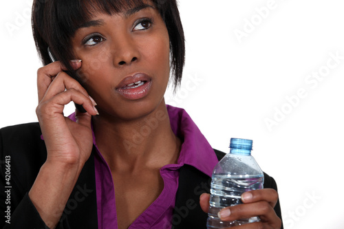 A black businesswoman on the phone waiting to take a sip.