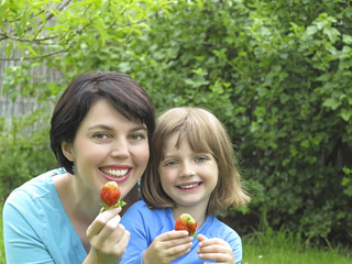 happy mother and her daughter eating strawberries in the garden