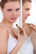 Woman applying lip-stick in mirror