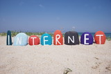 Internet, word on colourful stones over the sand