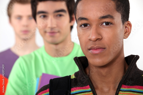 three male students posing in a line