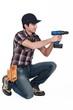 A kneeled handyman drilling.