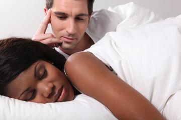 Man watching his girlfriend sleep