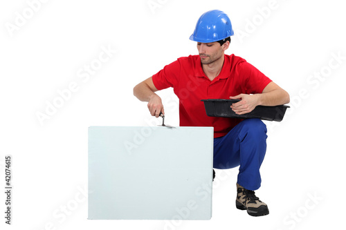 Bricklayer cementing a board left blank for your message