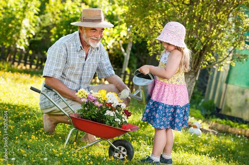 Leinwanddruck Bild Happy grandfather with his granddaughter  in the garden