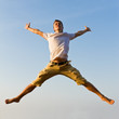 Happy young man jumping against blue sky background