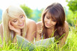 Two young beautiful smiling women reading book, sitting on grass