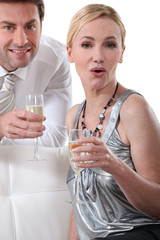 Blond woman holding champagne glass surprised expression